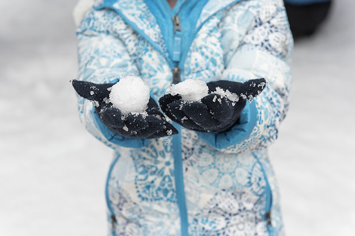 Child's hands wearing mittens and holding snow at CMOSC annual Snow Days Event in 2019