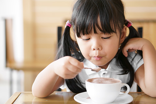 toddler using a spoon to stir and drink a hot chocolate drink