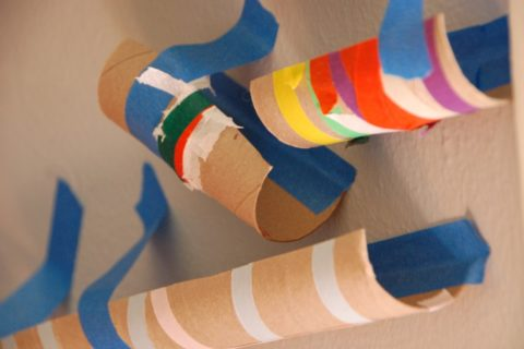 A marble run course handmade by children out of empty paper towel rolls and painters tape