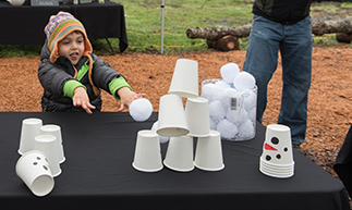 child knocking over cups with thrown snowball