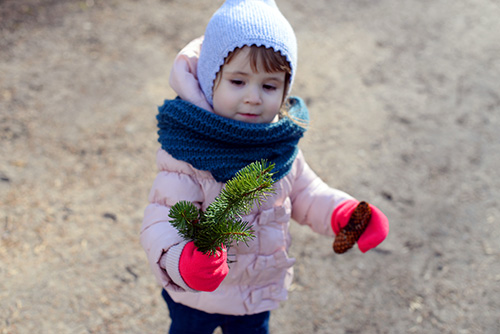 young child holding coniferous tree branch