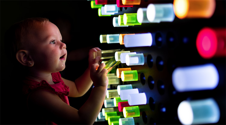 Toddler laying with interactive light peg wall exhibit at the children's museum of sonoma county