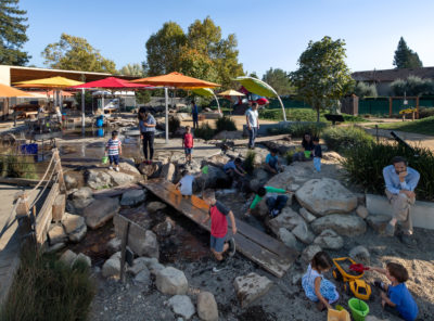 children playing at the Children's Museum of Sonoma County outdoors in the Russian River Waterway interactive exhibit.