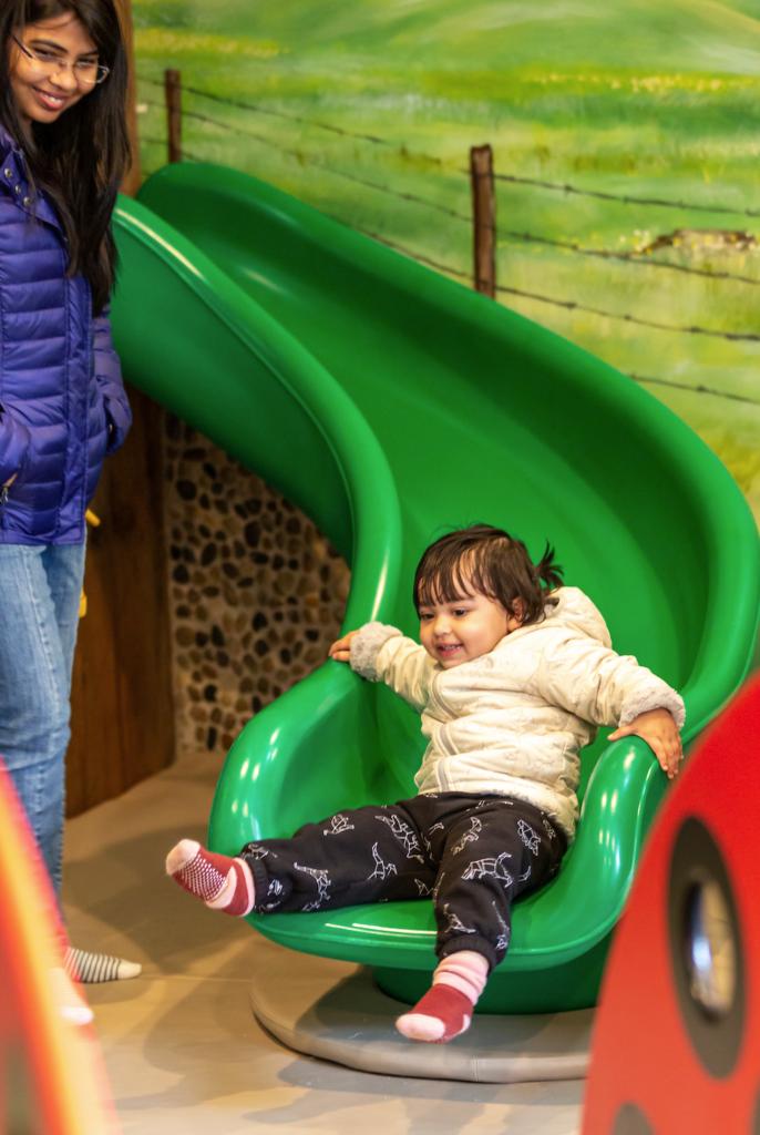 child sliding down slide at totopia