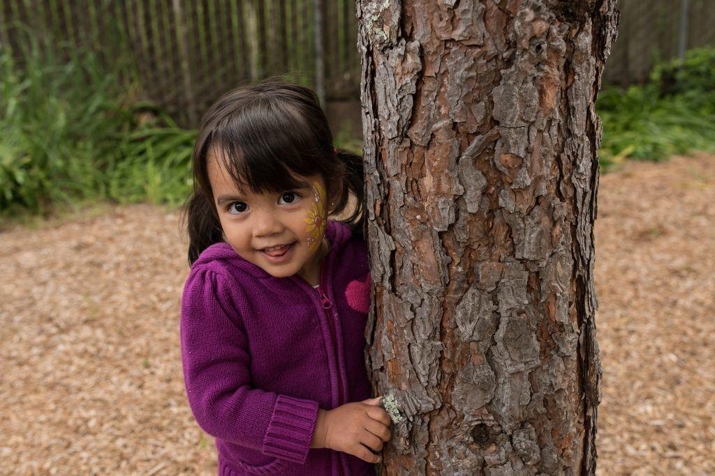 child next to tree