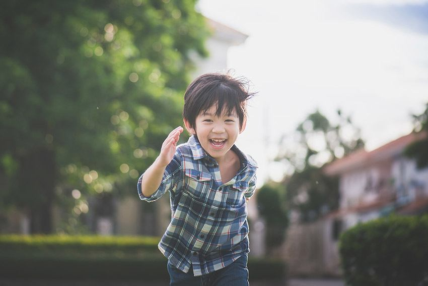 Little boy running around, laughing and playing outside