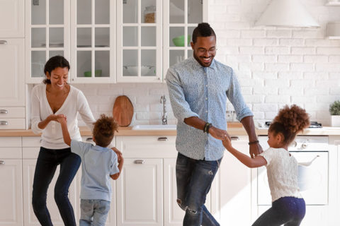 Happy parents and two toddlers dancing to music in kitchen, holding hands, having fun and laughing
