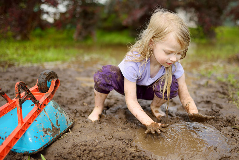 Toddler playing in the mud with a wheel barrel
